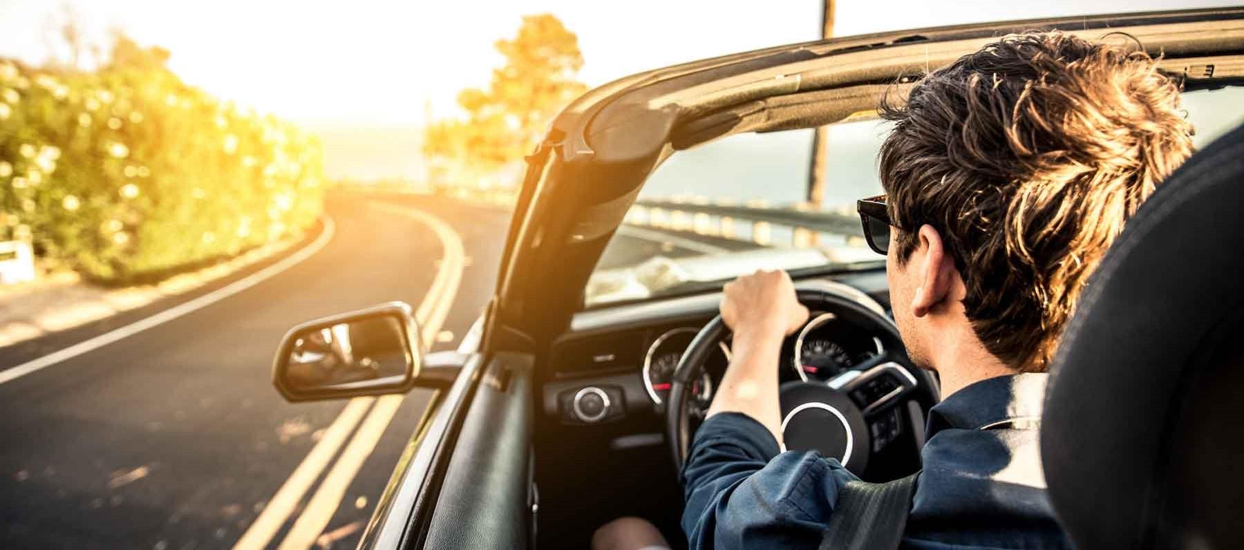 Mann genießt Fahrt im Cabrio.
