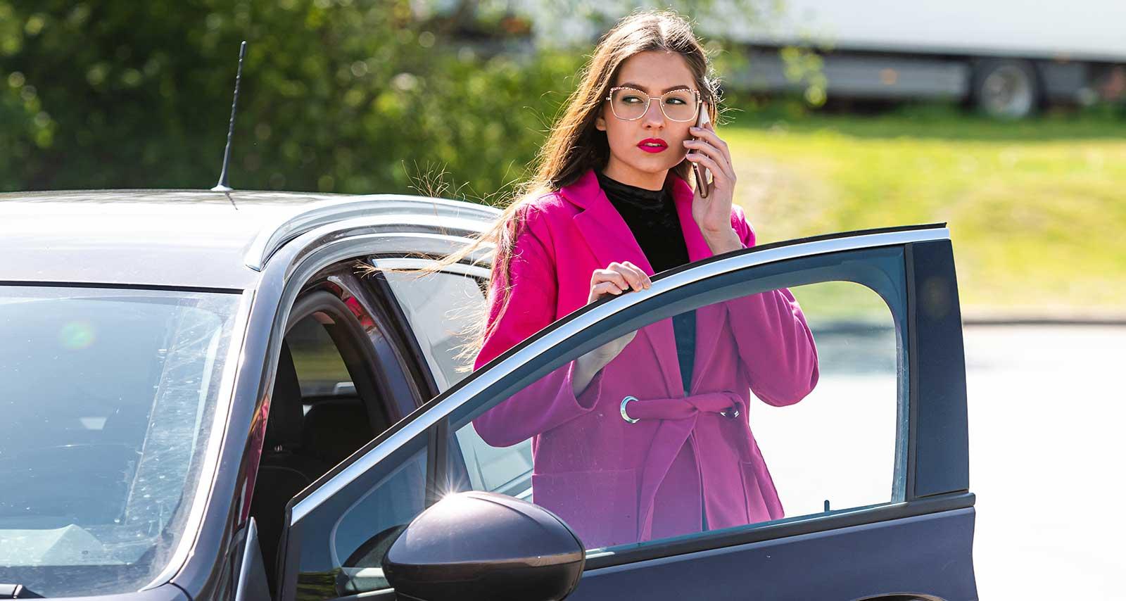 Frau telfoniert vor ihrem Firmenwagen.