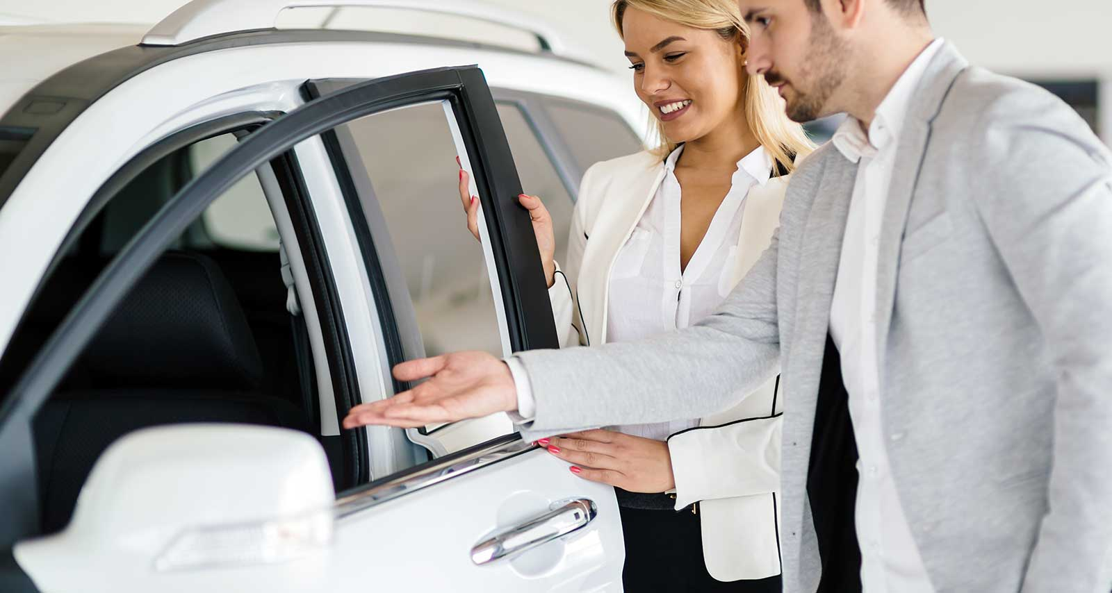 Mann und Frau übernehmen Auto-Abo Fahrzeug.
