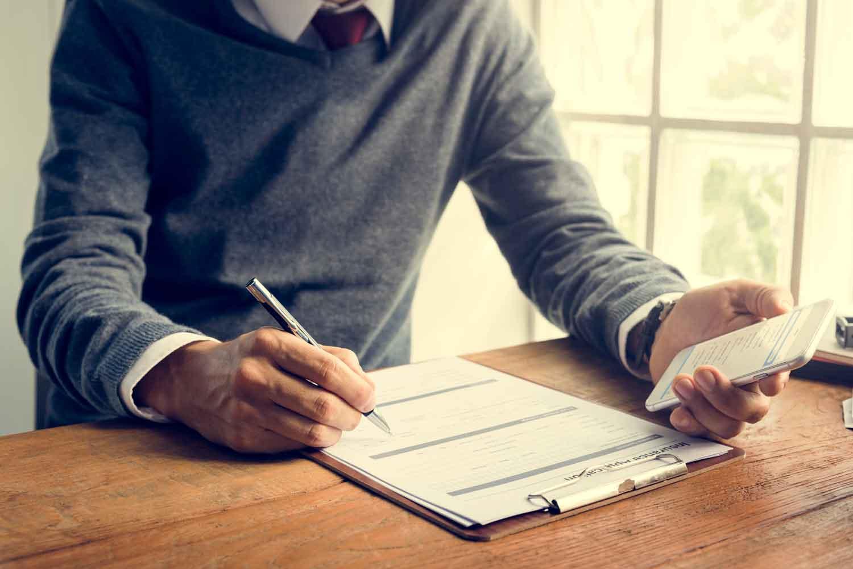 Ein Mann unterzeichnet seine KFZ-Versicherung.