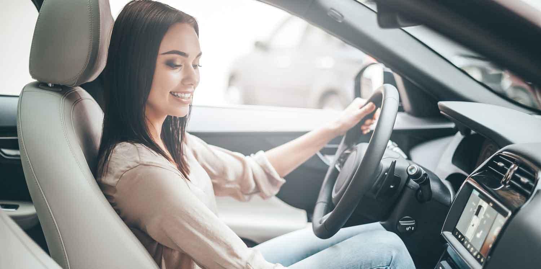 Frau hört Musik durch Carplay in ihrem Auto-Abo von ViveLaCar.