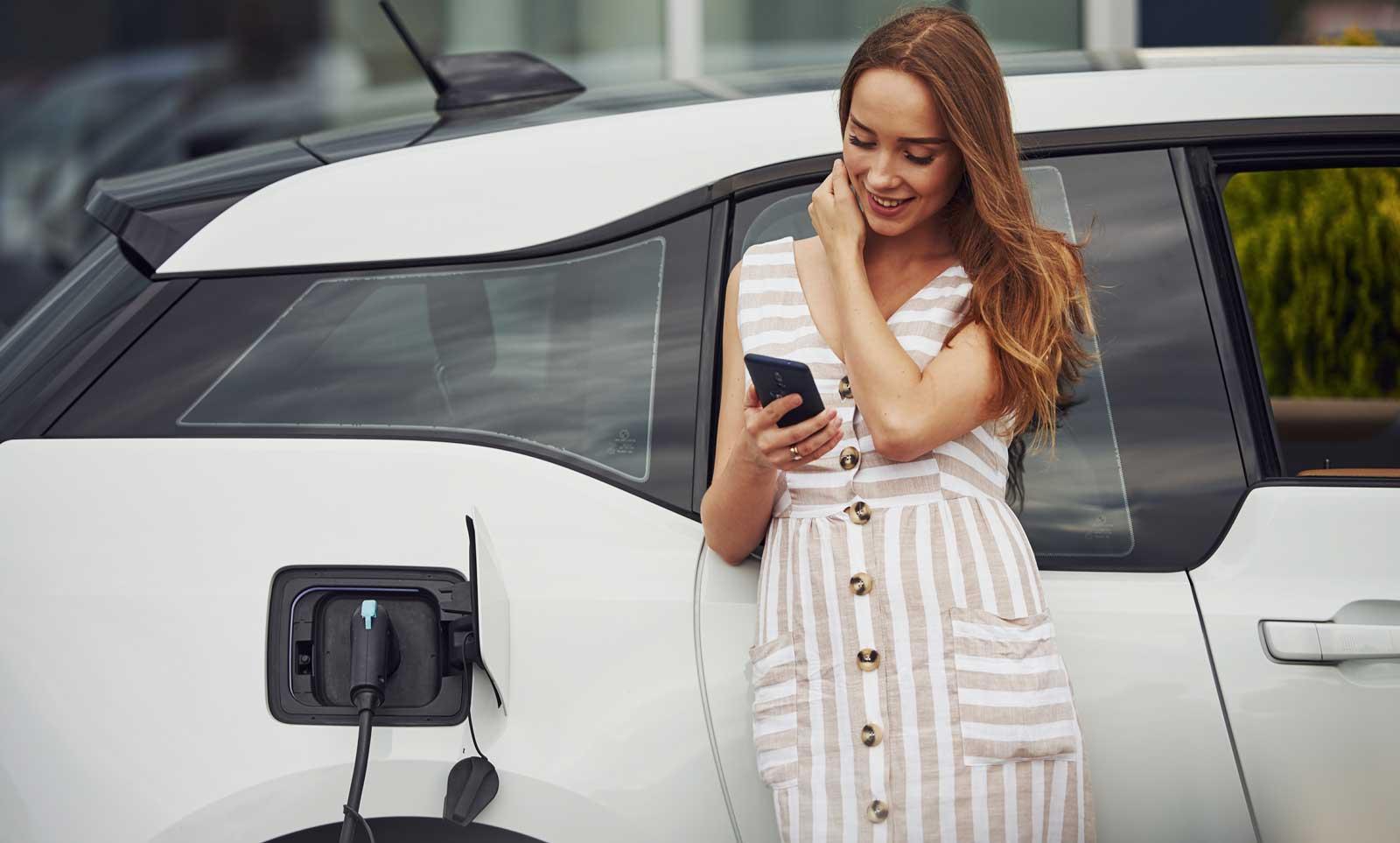 Frau steht vor ihrem ViveLaCar Auto-Abo und lädt ihren Abo-Elektro.